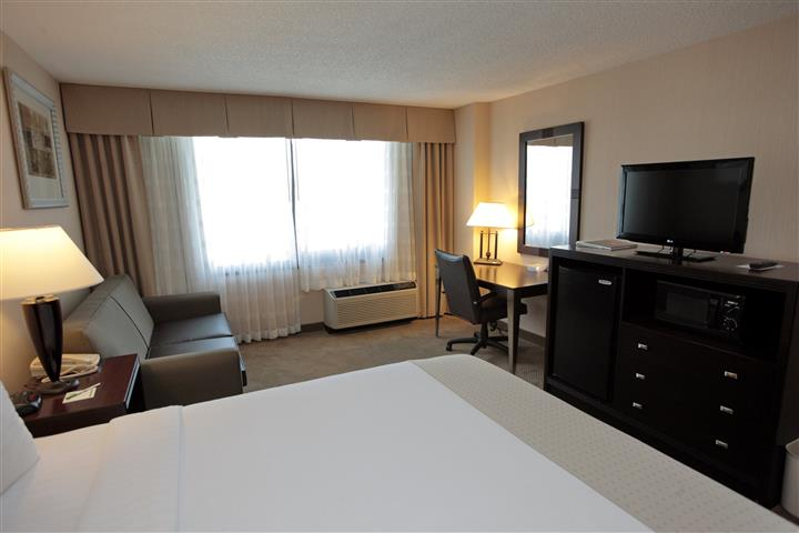 Hotel room with bed, chair, dresser with TV, desk and window.