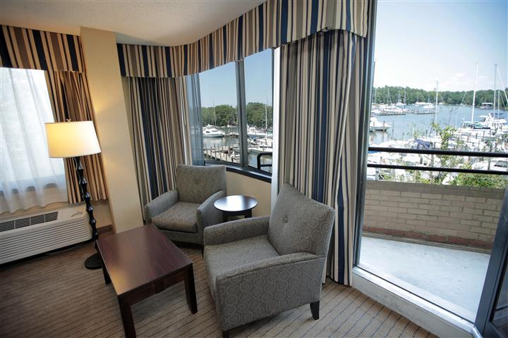 Hotel room with open door leading to balcony with view of boats in marina.