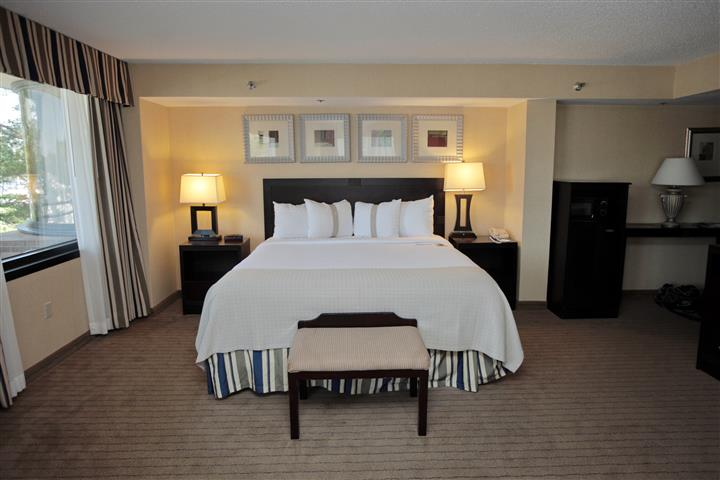 Hotel room with king size bed, end tables with lamps, dresser and window.