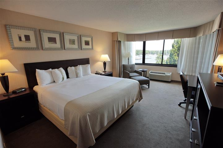 Hotel room with king size bed, night tables, lamps, dresser and window with view of marina