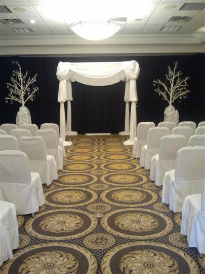 Wedding ceremony setup with covered chairs in banquet room