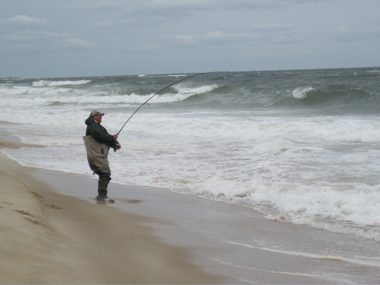 Man surfcasting on cloudy day