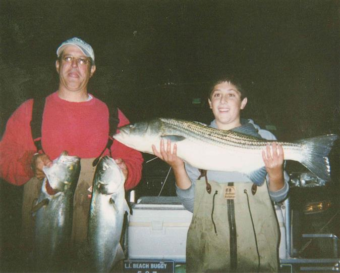 Man and teenage boy holding fish at night