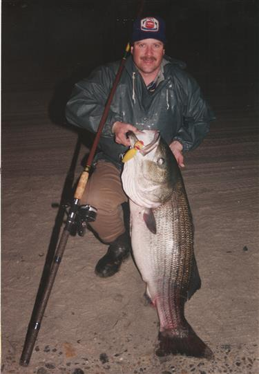 Man kneeling on beach holding fish at night