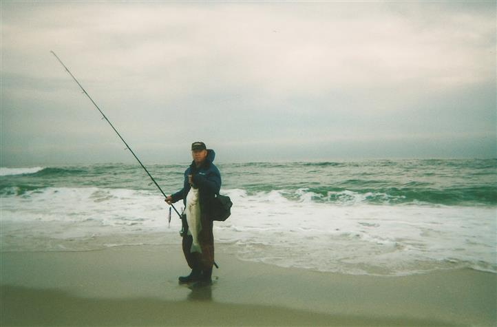Man standing at edge of water holding fish