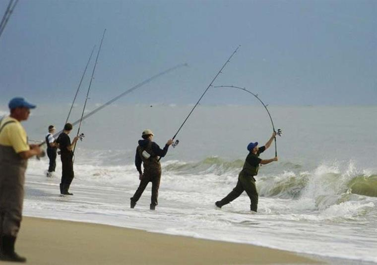 4 men fishing on beach
