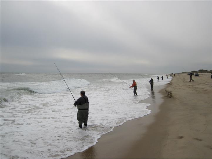 Three men surfcasting on cloudy day