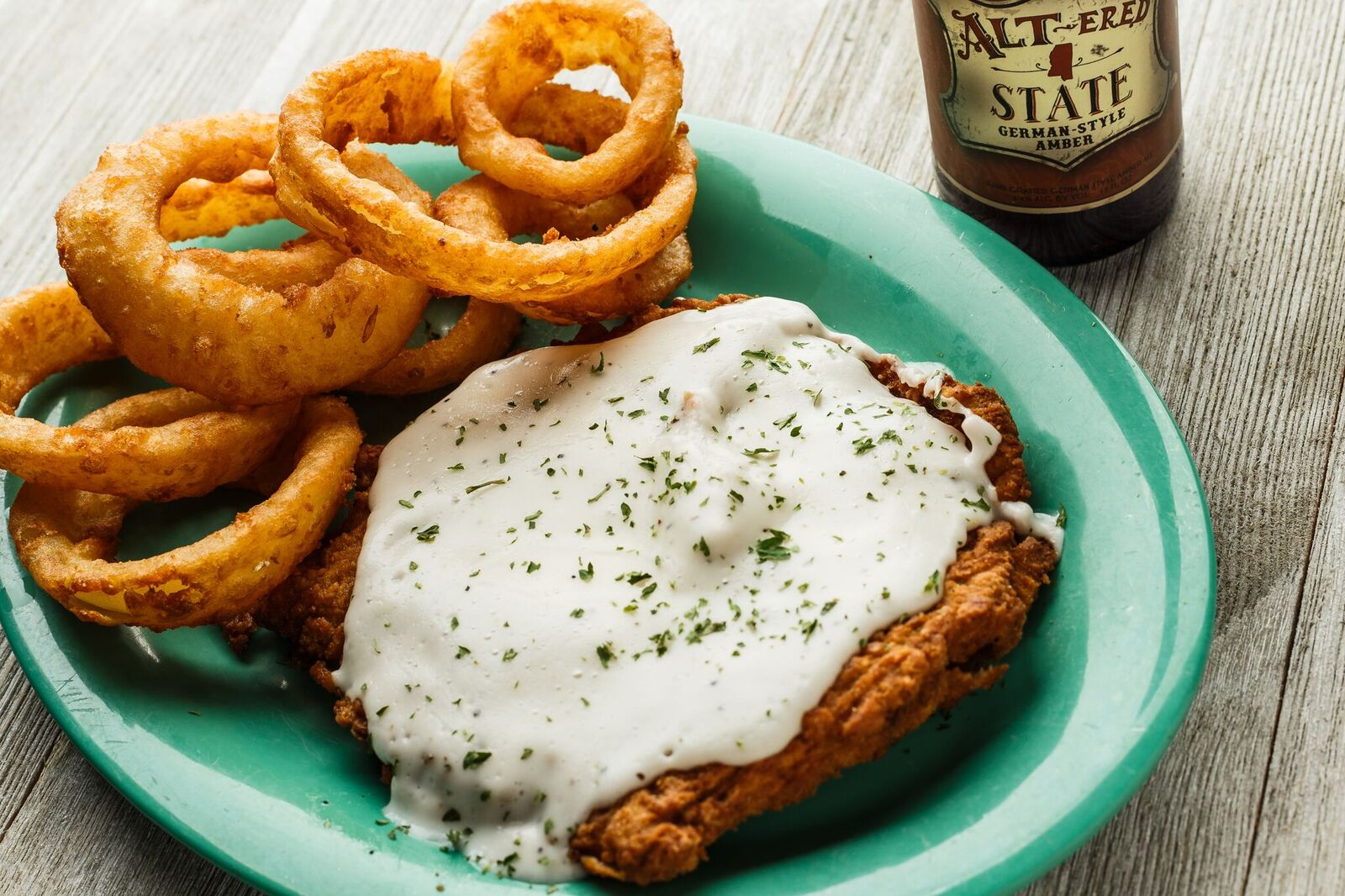 Fried chicken topped with white sauce and a side of onion rings