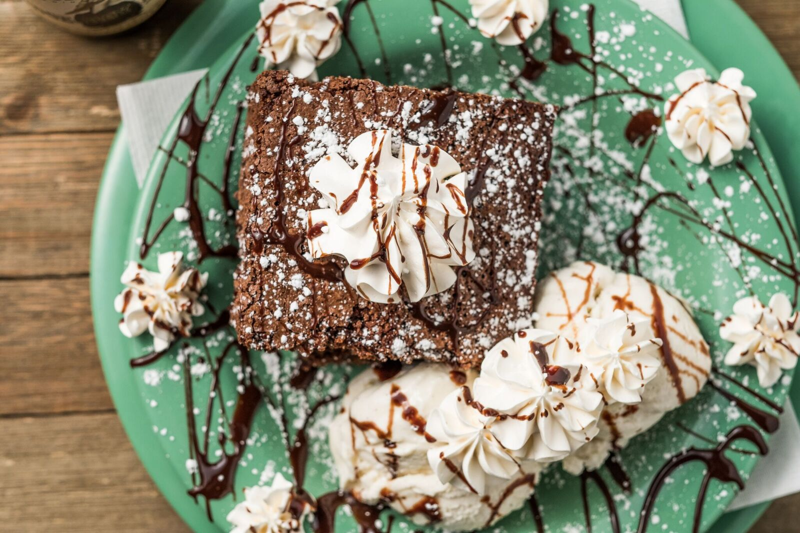Brownie topped with whipped cream and chocolate fudge