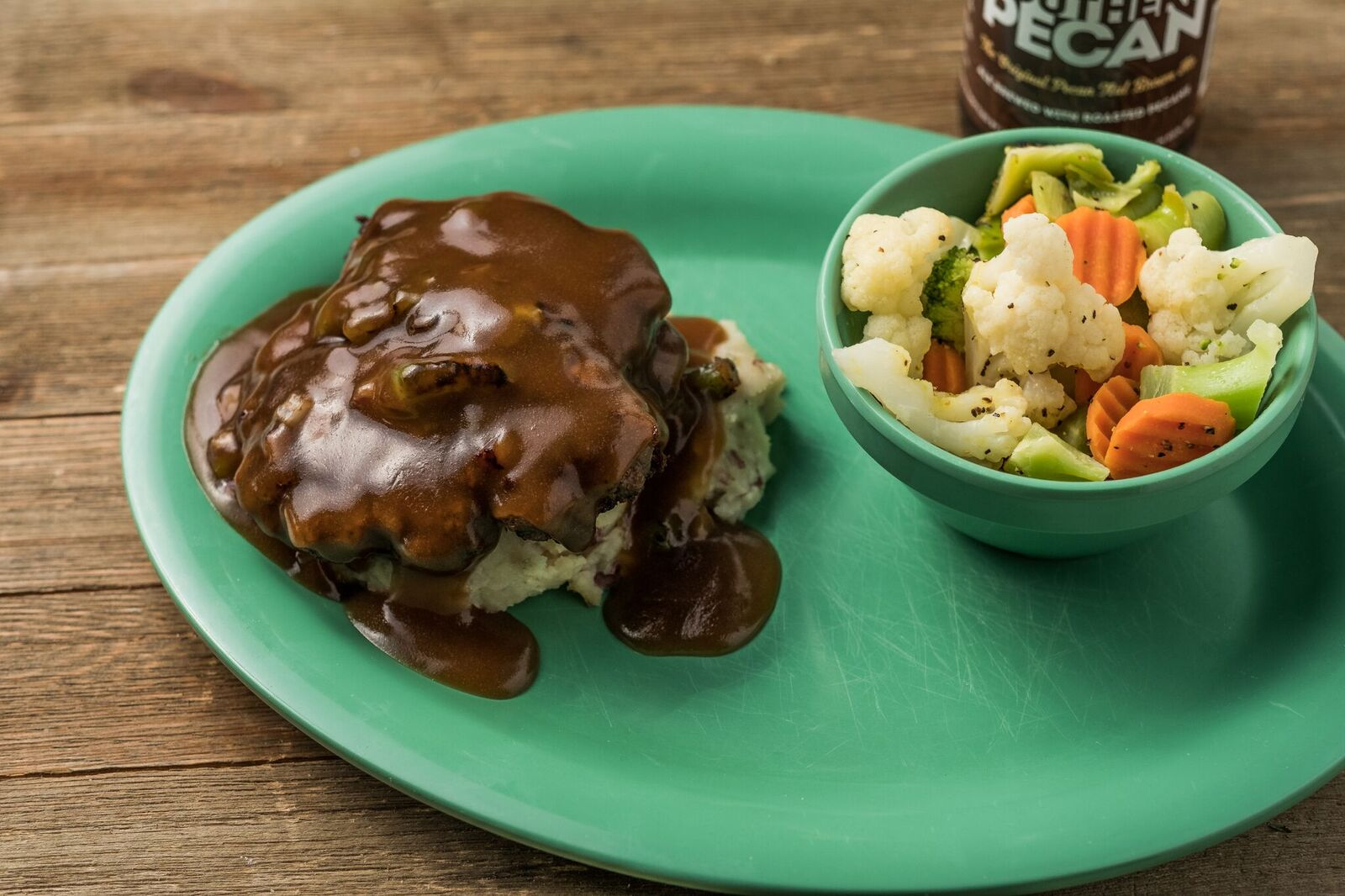 Mashed potatoes topped with brown gravy with a bowl of vegetables