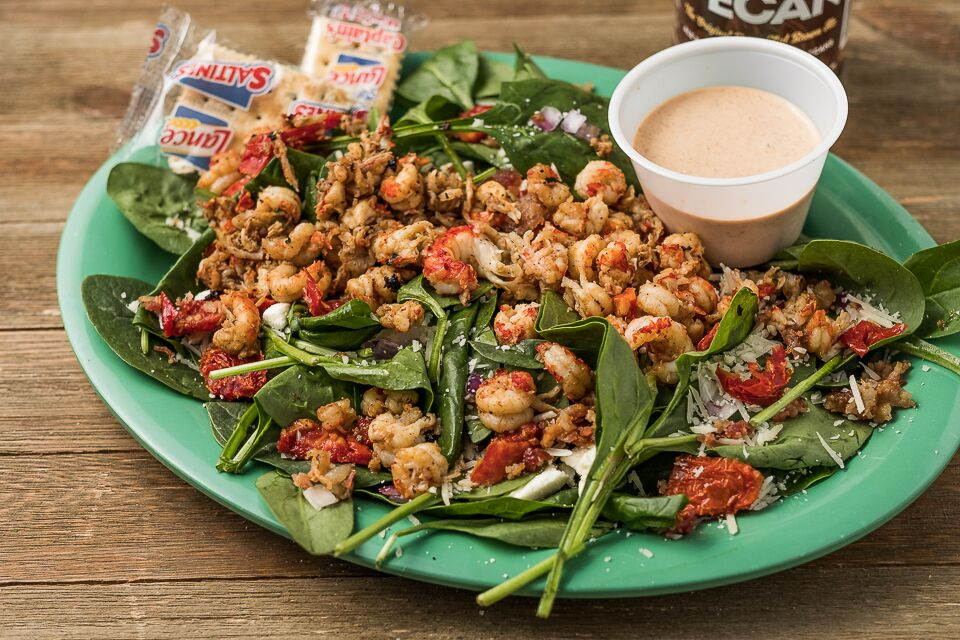 A spinach salad with shrimp, shredded cheese and red sauce marinara sauce