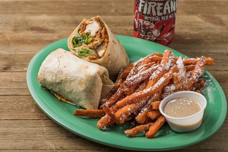 Crispy chicken and lettuce in a wrap with a side of sweet potato fries