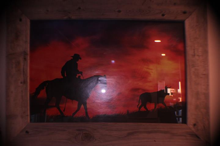 wall art with cowboy on a horse with cattle