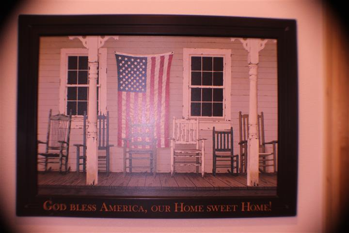 """Wall art with front porch that reads """" God bless america, our home sweet home"""""""