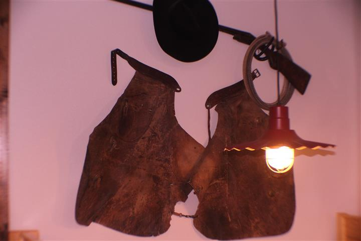 leather chaps, hat and rifle wall art