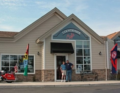 owners of countryside cafe posing for picture in front of restaurant
