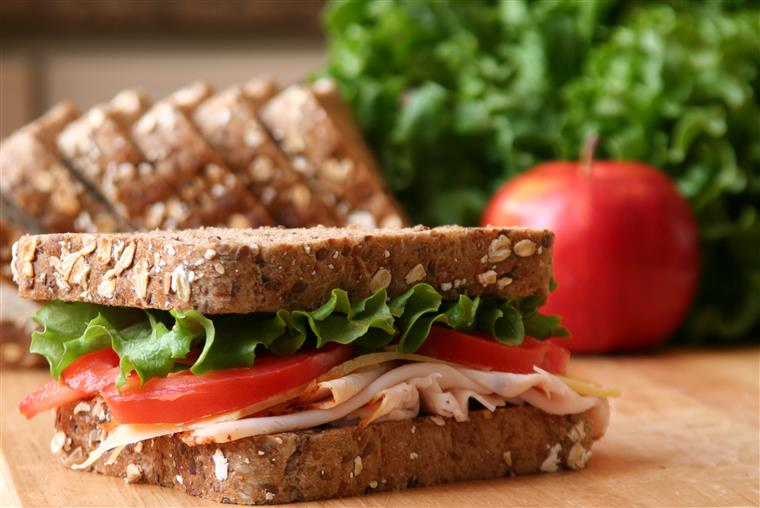 turkey sandwich topped with lettuce and tomato. slices of bread, lettuce and a tomato are in the background.
