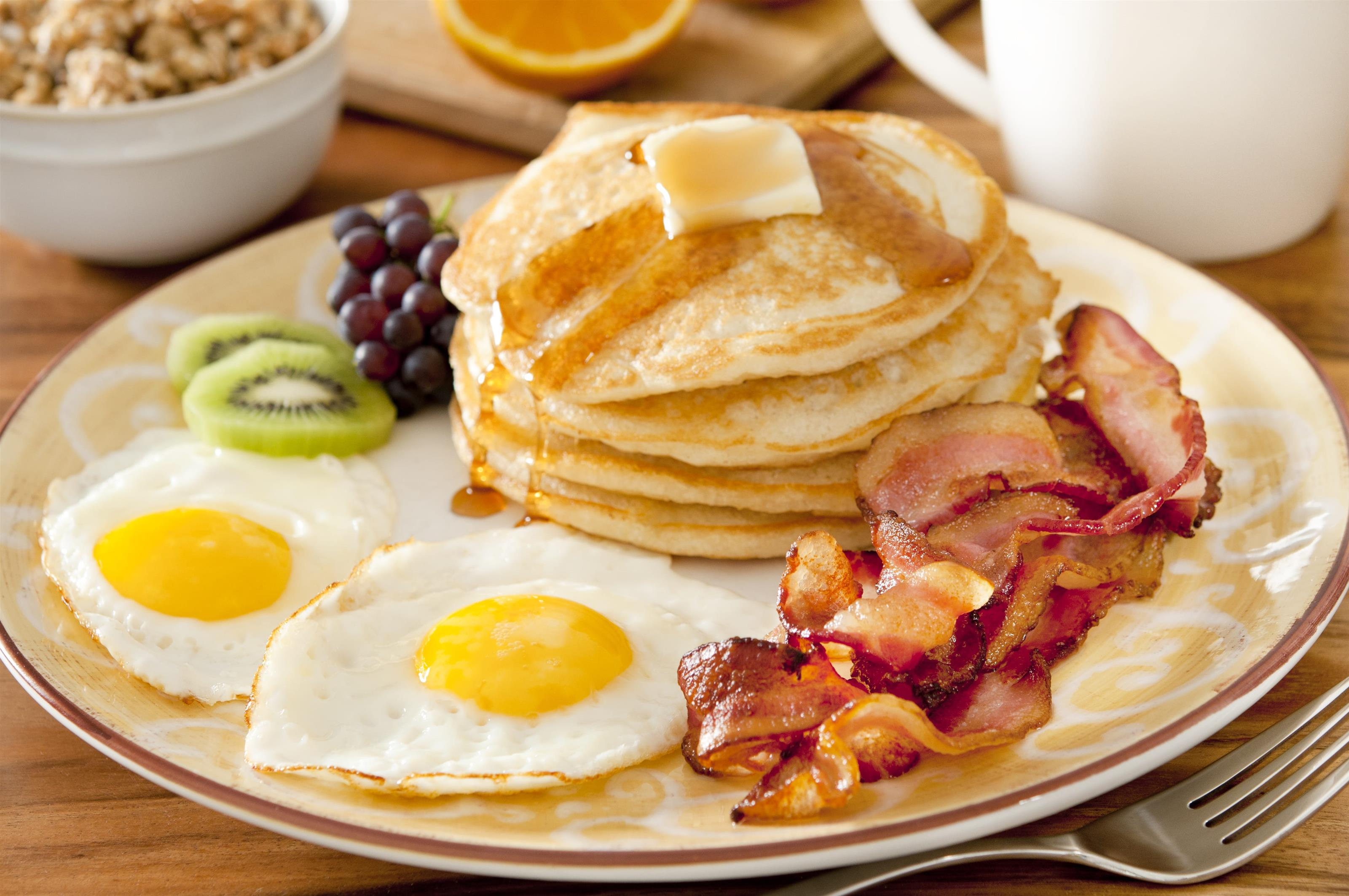 Closeup of a breakfast plate with pancakes, eggs, bacon and fruit
