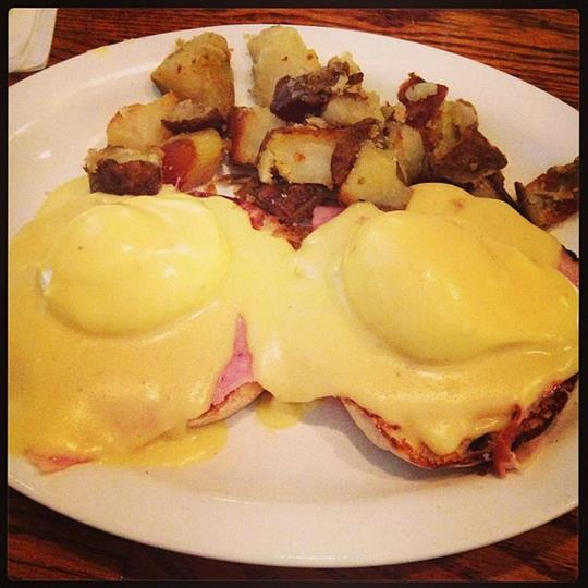 eggs benedict on english muffins with a side of cooked potatoes
