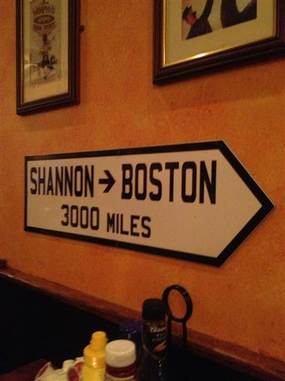interior sign thats pointing and says shannon boston, 3000 miles away