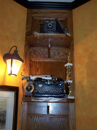 interior cabinet displaying a vintage camera and typewriter