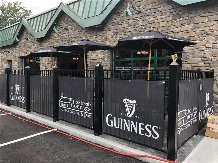 exterior fence to the irish cottage with the establishments logo and guinness logo printed on banners