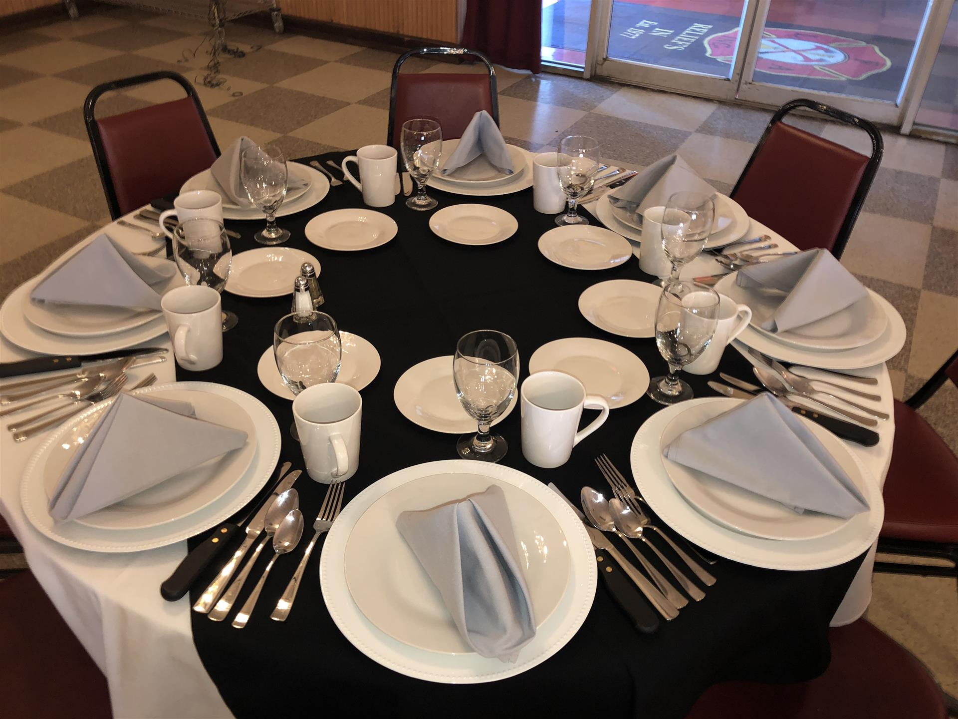 Round table with black tablecloth, plates and silverware