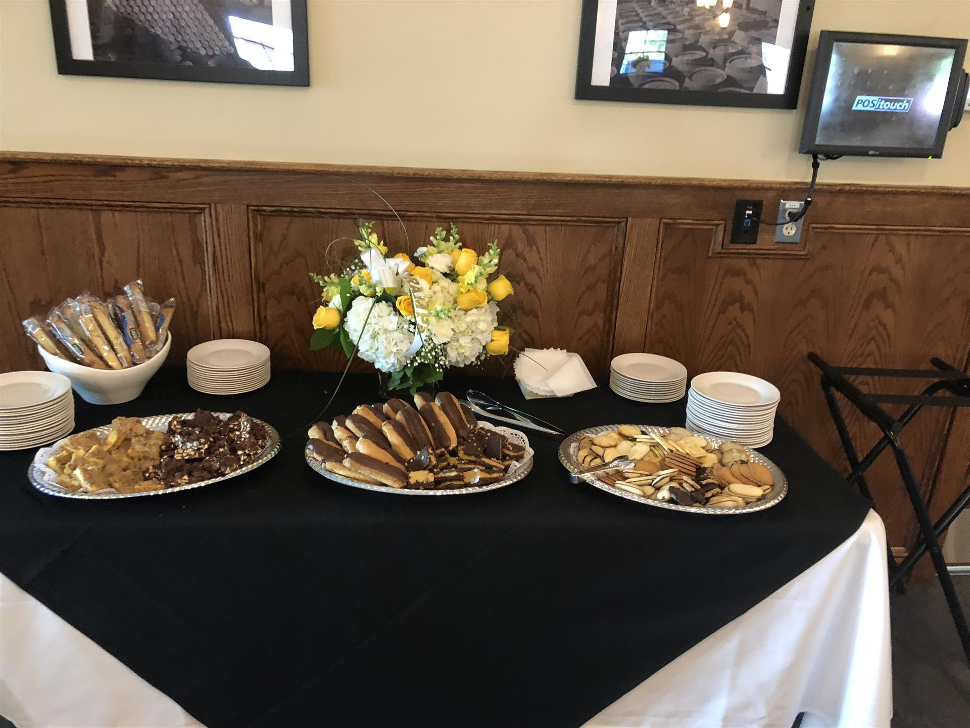 catering assortment of various desserts on a table with plates and napkins