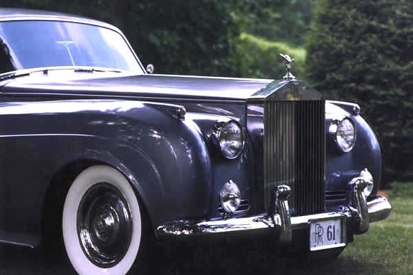Front end of rolls royce parked on grass.