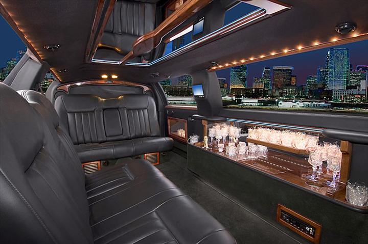 Inside view of limousine with seats and mini bar. Skyscrapers at night seen through windows.