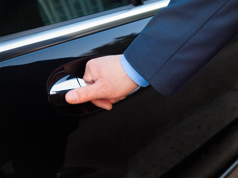 Hand of chauffeur opening door of black limousine