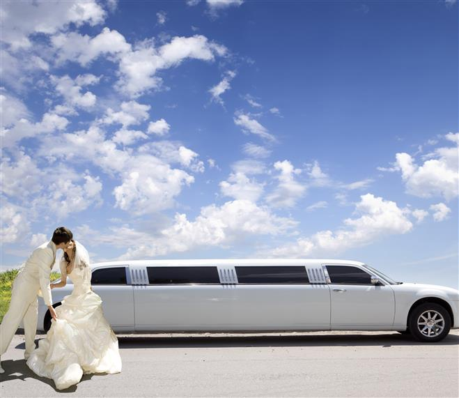 Bride and groom kissing near stretched limousine in front of blue sky with high clouds