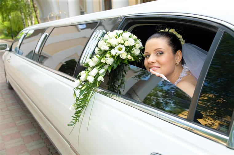 Bride with flowers peering out of stretched limousine window.