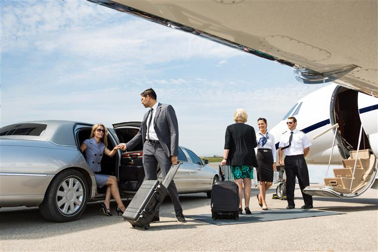 People exiting limousine in front of private jet.