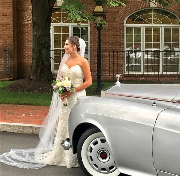 Bride standing in front of rolls royce with brick building in background