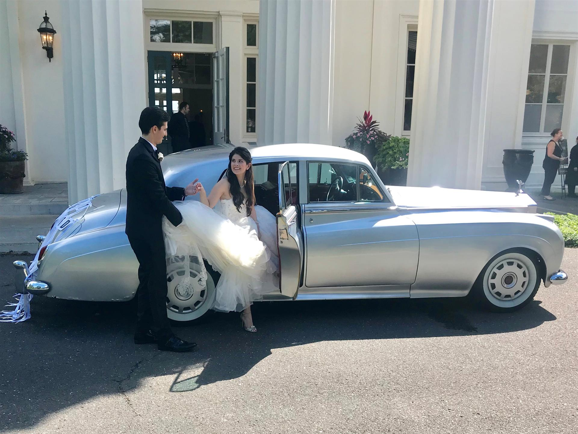 Groom helping bride out of rolls royce in front of white columned building