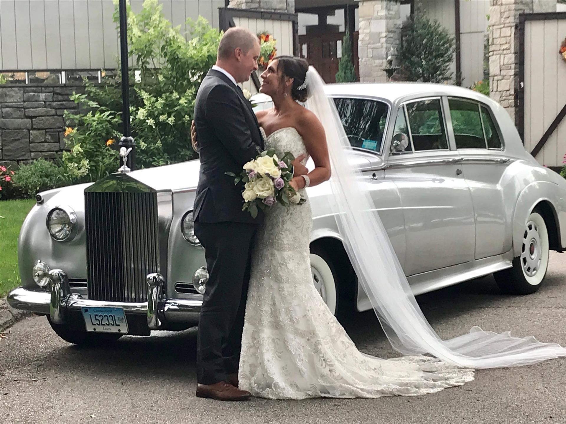 Bride and groom gazing at eachother in front of rolls royce