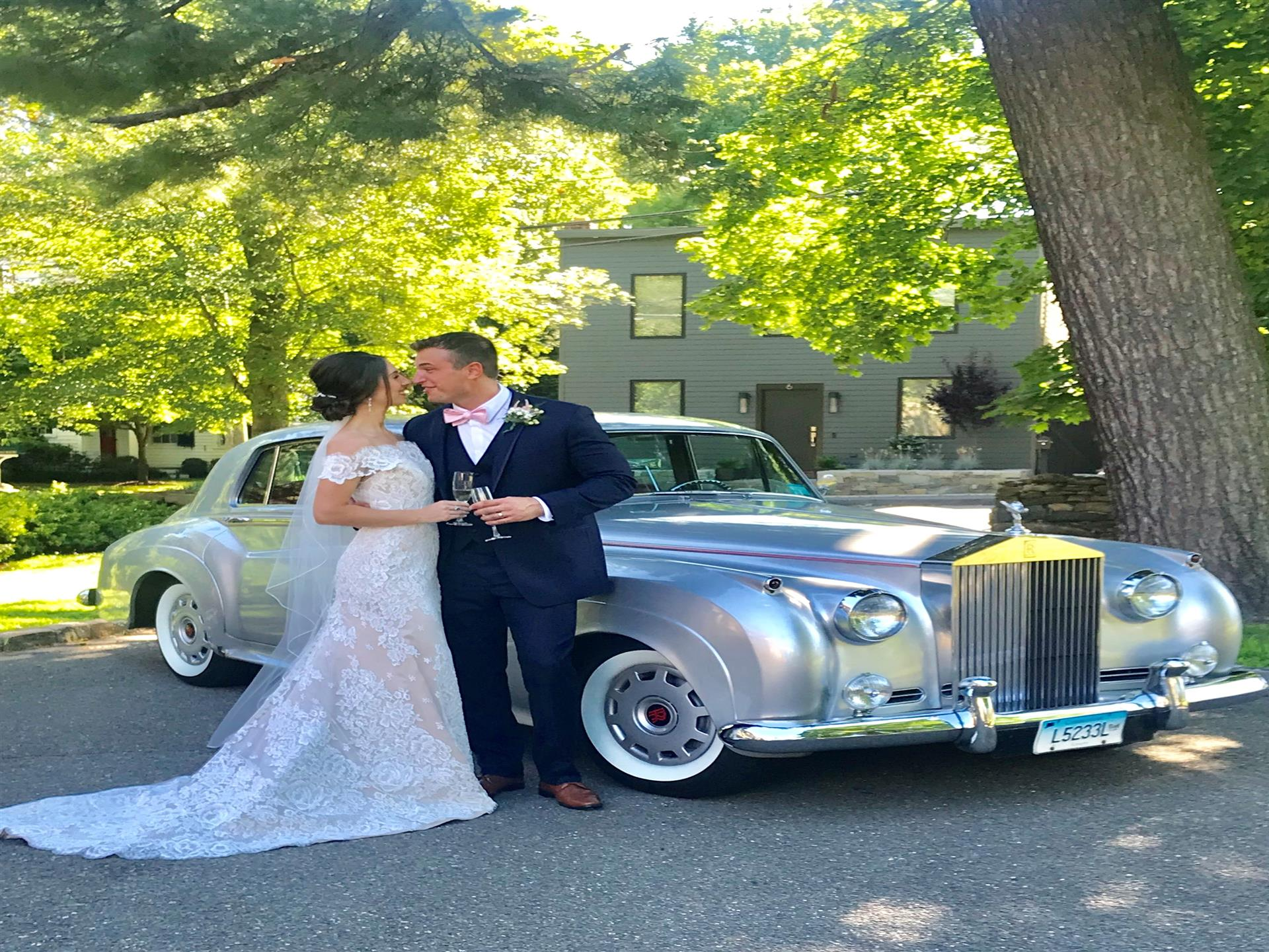 Bride and groom with champagne glasses standing next to rolls royce in parking lot with green building in background