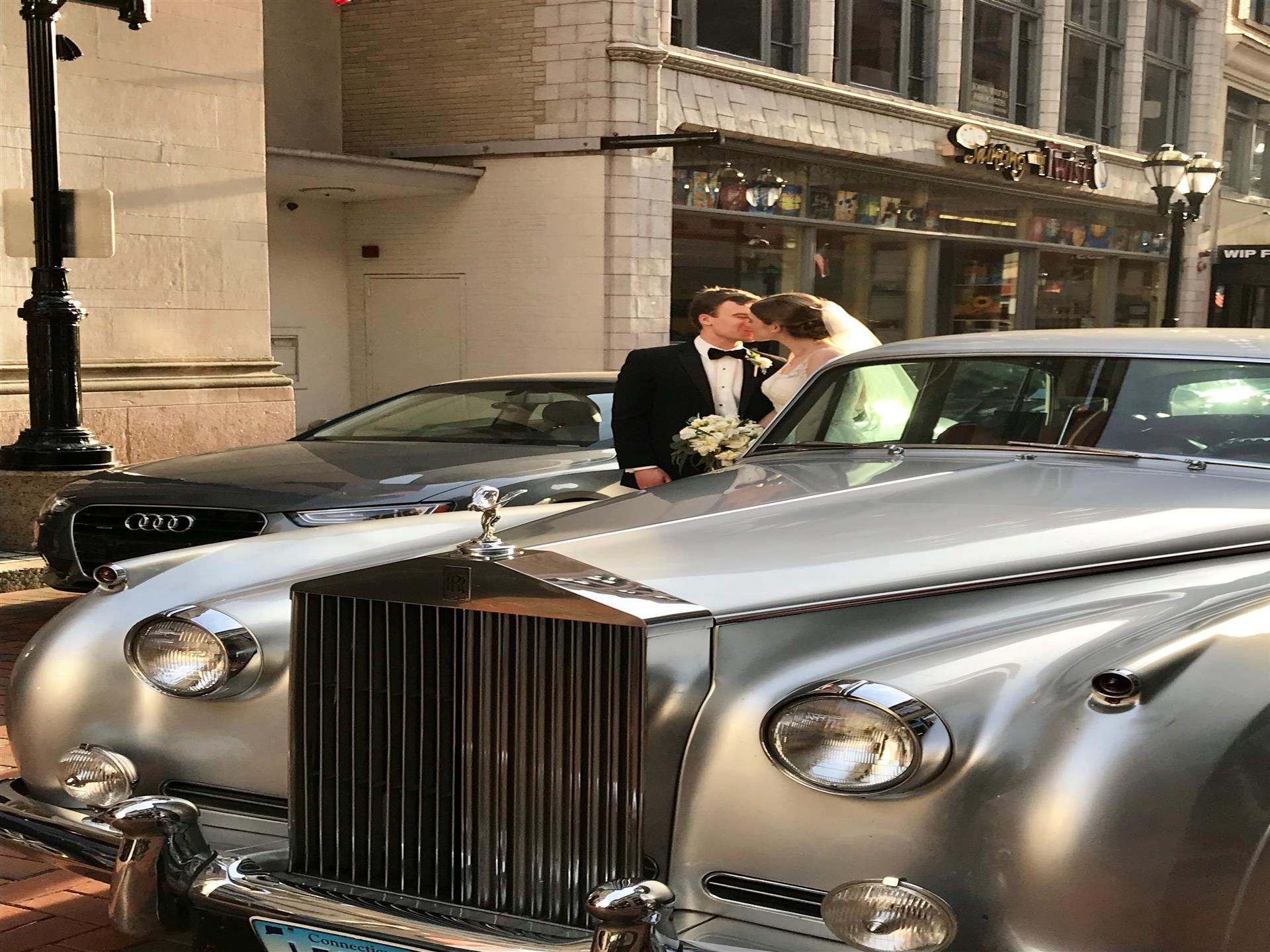 Bride and groom standing next to rolls royce in street kissing