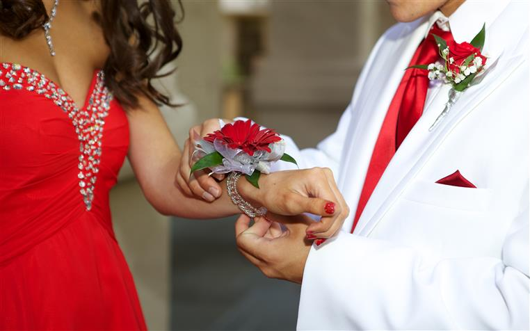 Teens going to prom. Girl in prom dress, boy in suit giving girl flowers.