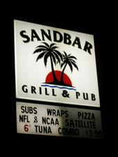 exterior street sign for sandbar grill & pub near a street