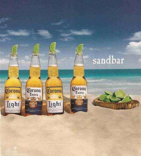 various corona bottles in sand at the beach with a side of lime wedges