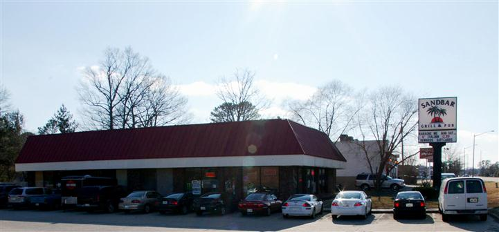 exterior building of sandbar grill & pub with a filled parking lot
