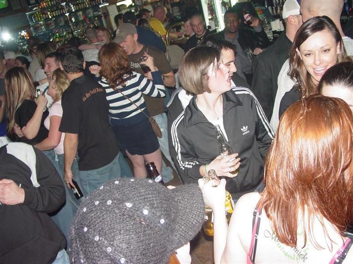 crowd of people hanging out inside the bar drinking and laughing together