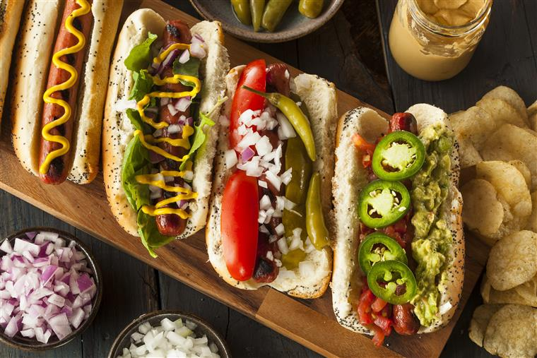 Hot dogs with assorted condiments on wood cutting board.