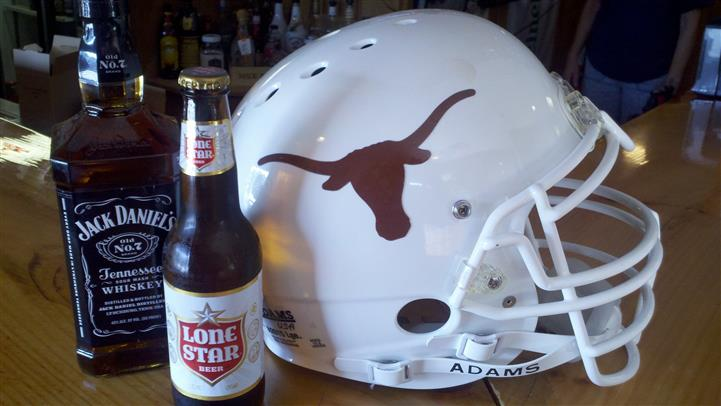 A bottle of Lone Star beer next to Texas Longhorns football helmet
