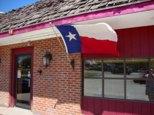 Storefront of the texas barbecue with texas flag