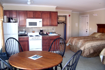 Kitchen with table and bed inside the suite