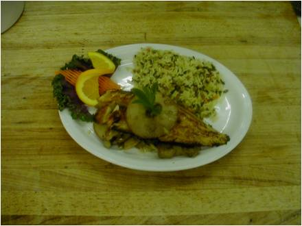 Fish with a side of rice and a orange slice