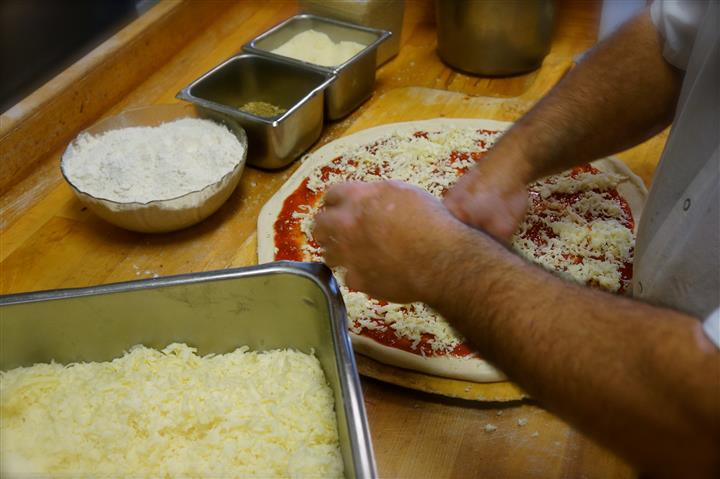 Pizza being prepared by a chef